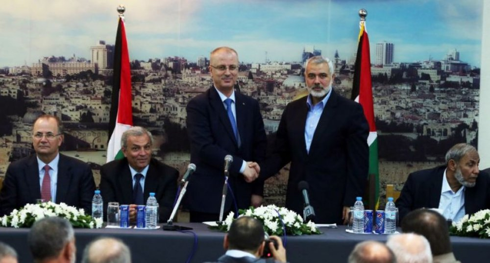 PA prime minister Rami Hamdallah and Hamas leader Ismail Haniyyah shaking hands in Gaza as Hamas formally hands over control of the Strip to the PA